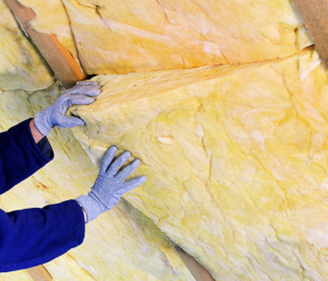 A person wearing blue gloves installs insulation in ceiling