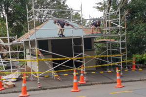 Two Newton Roofing team members laying down the corrugated iron for a recent roofing job in Wellington