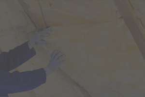 A person installing insulation into a roof