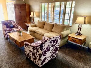 the large living room of Suite 1 featuring a 3 person sofa, two cow print chairs, a coffee table, two end tables with lamps and a large armoire.