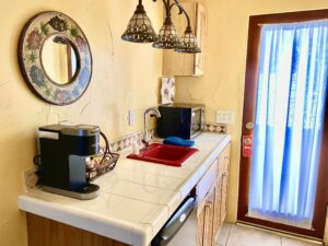 the kitchenette of Suite 3 featuring a Refrigerator, Microwave, and Keurig Coffeemaker with a glass door behind it.