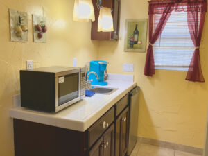 The kitchenette of suite 6 featuring a sink, refrigerator, microwave, and a Keurig Coffeemaker.