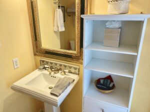 the vanity area of suite 7 showing a pedestal sink and a towel cabinet