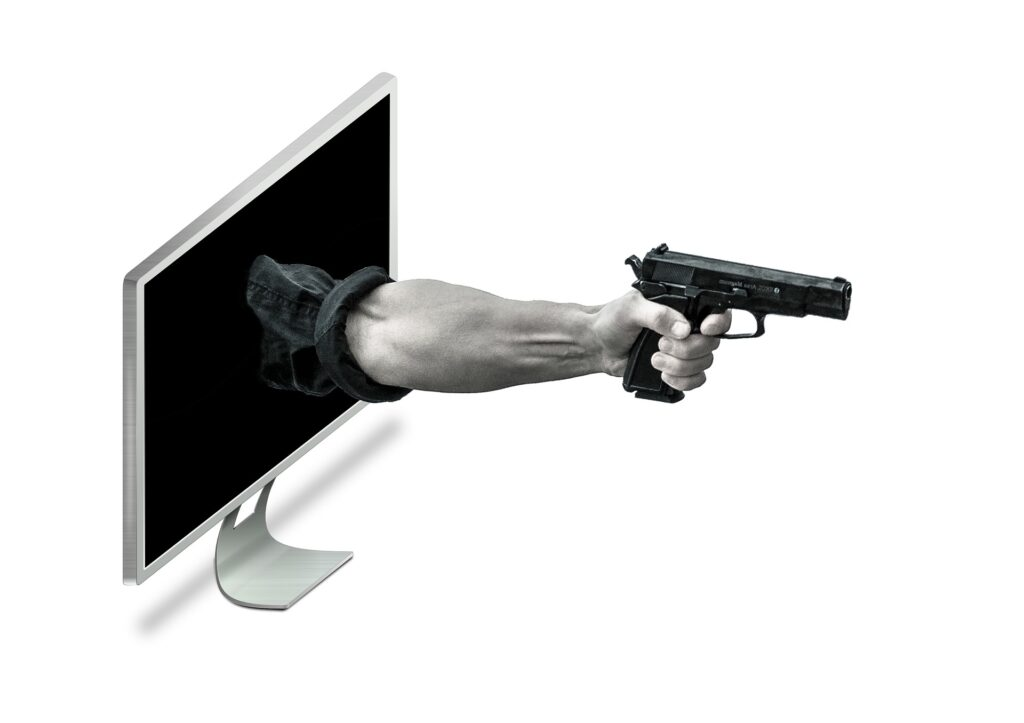 workplace violence insider threat with arm holding a pistol extended from a computer screen
