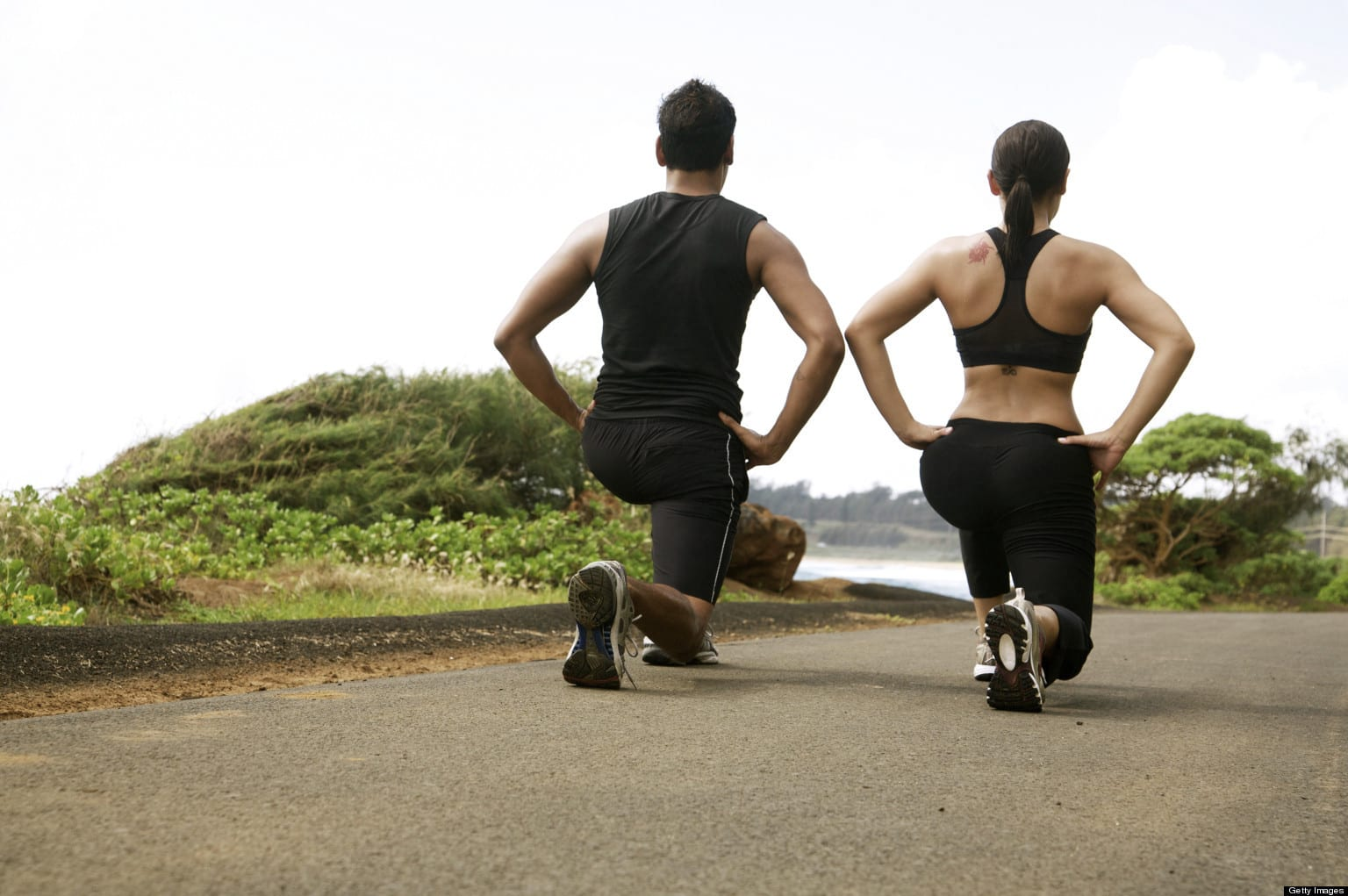 Hawaii, Kauai, Kealia Beach, Young fit couple doing lunges or sqauts.