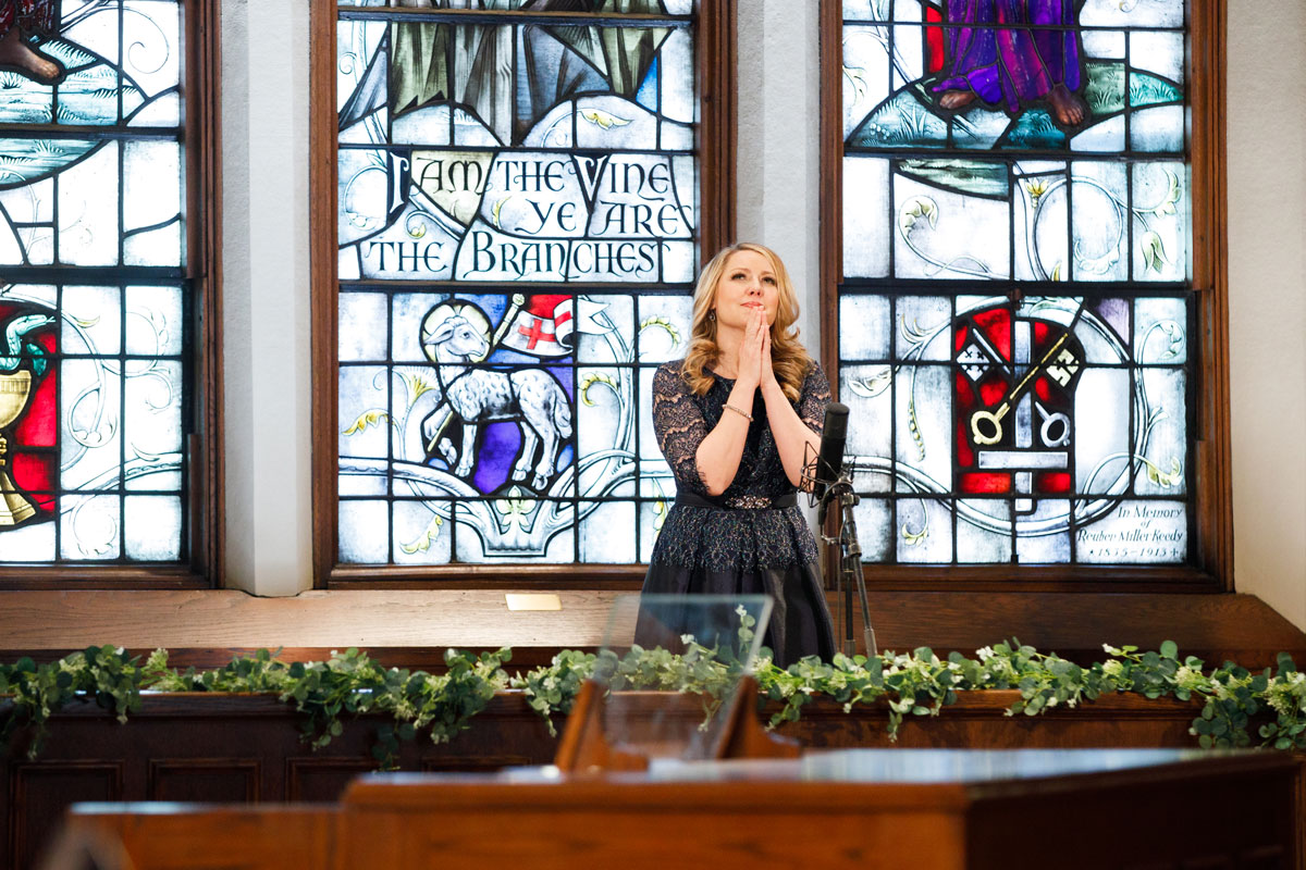 musician performs in front of church stained glass