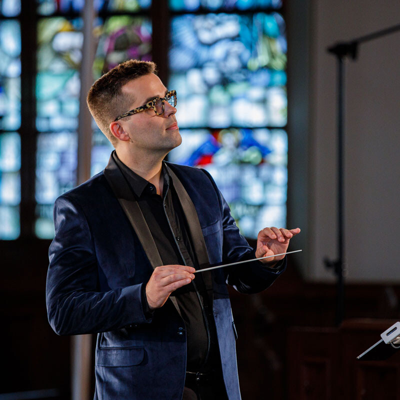 maestro conducts musicians in a church