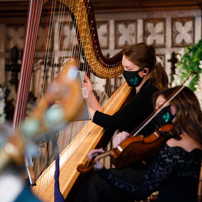 harpist and violinist play in a church