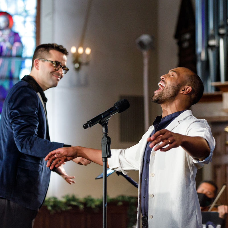 A conductor and musician perform in a church