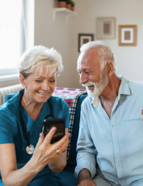 A home caregiver who supports an elderly man in his home and uses a smartphone together