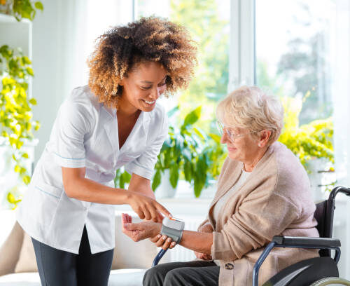 Female nurse checking the blood pressure of an old female patient sitting on wheelchair at home