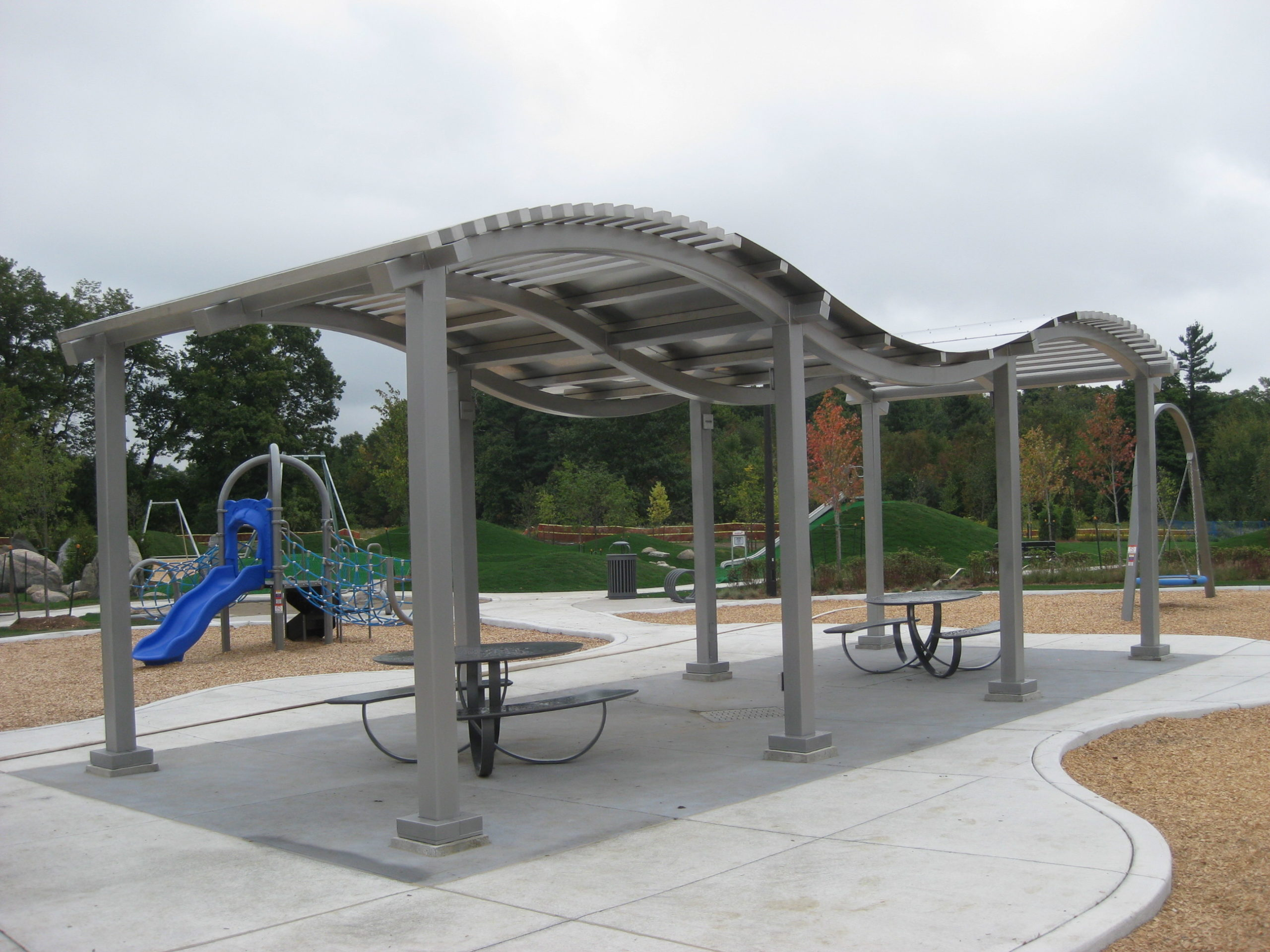 Shade structure with picnic benches under it.