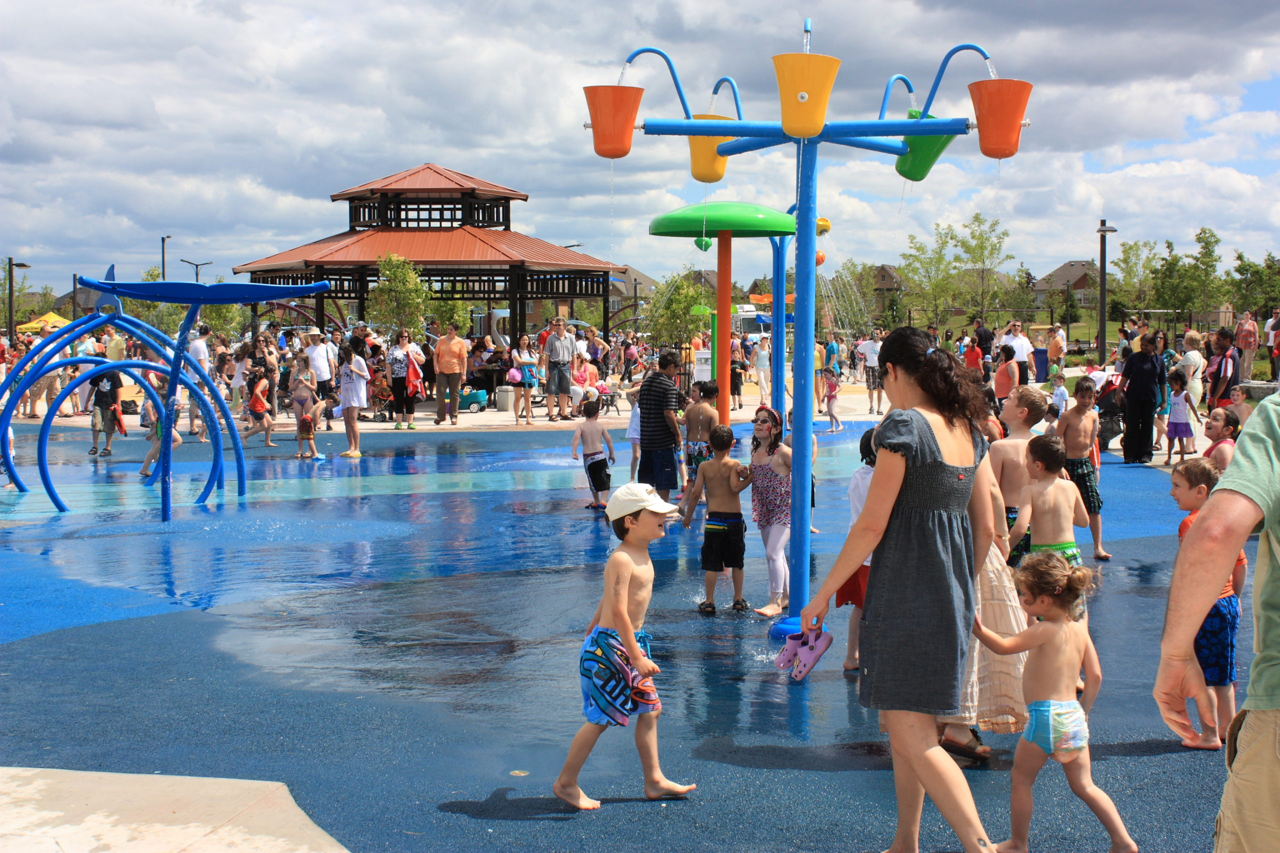 Large water park and splash pad with lots of children playing in it.