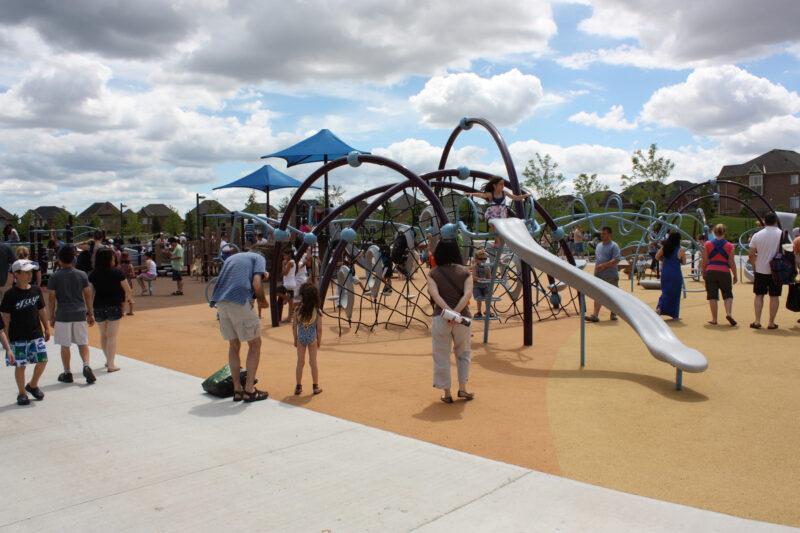 Children in playground with parents watching.