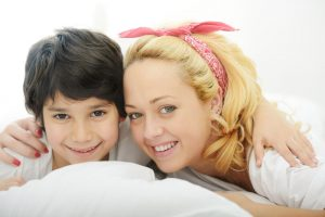 Happy blonde young mother with her son in bedroom bed