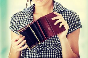Young woman shows her empty wallet. Bankruptcy