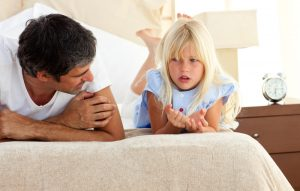 Little girl talking seriously with her father at home