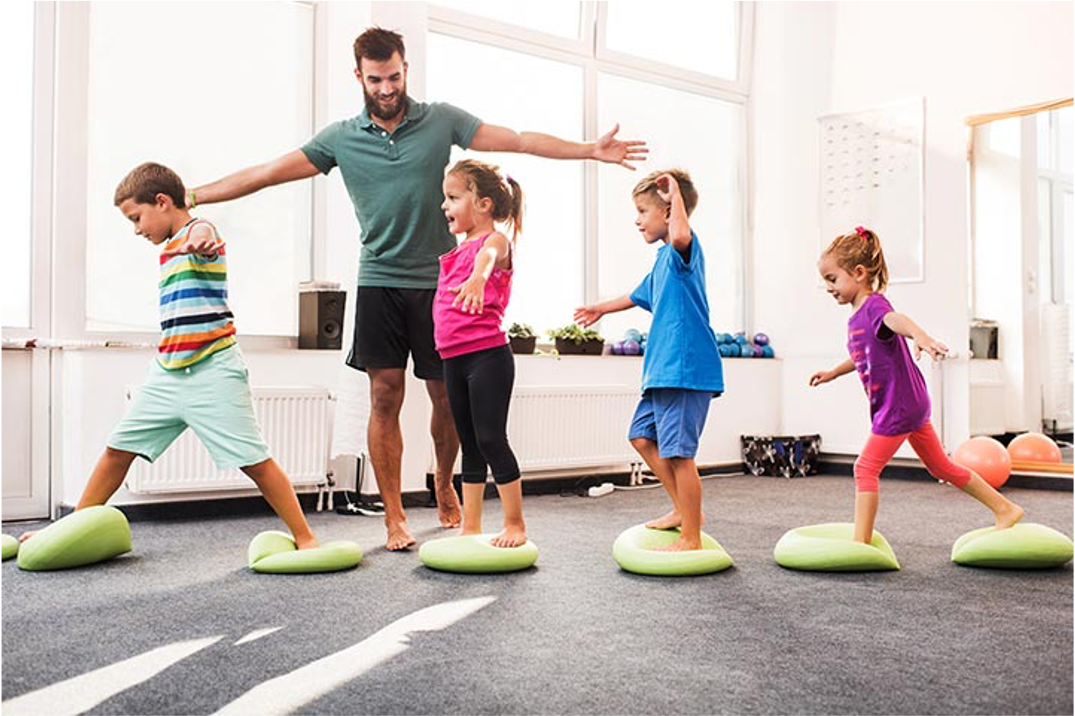 Kids with instructor on lime green small mats