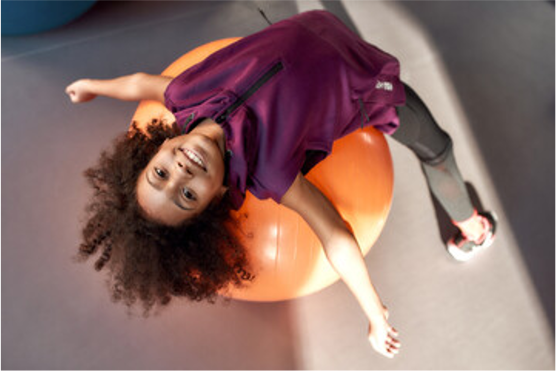 girl stretching on orange yoag ball