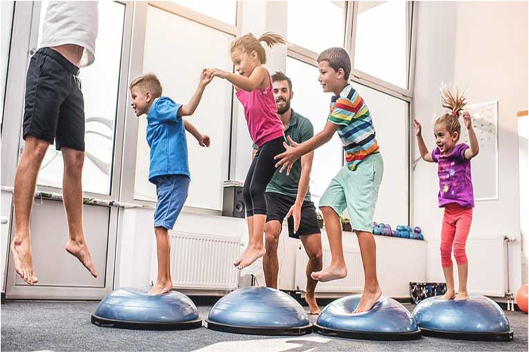 kids with instructor on blue round mats