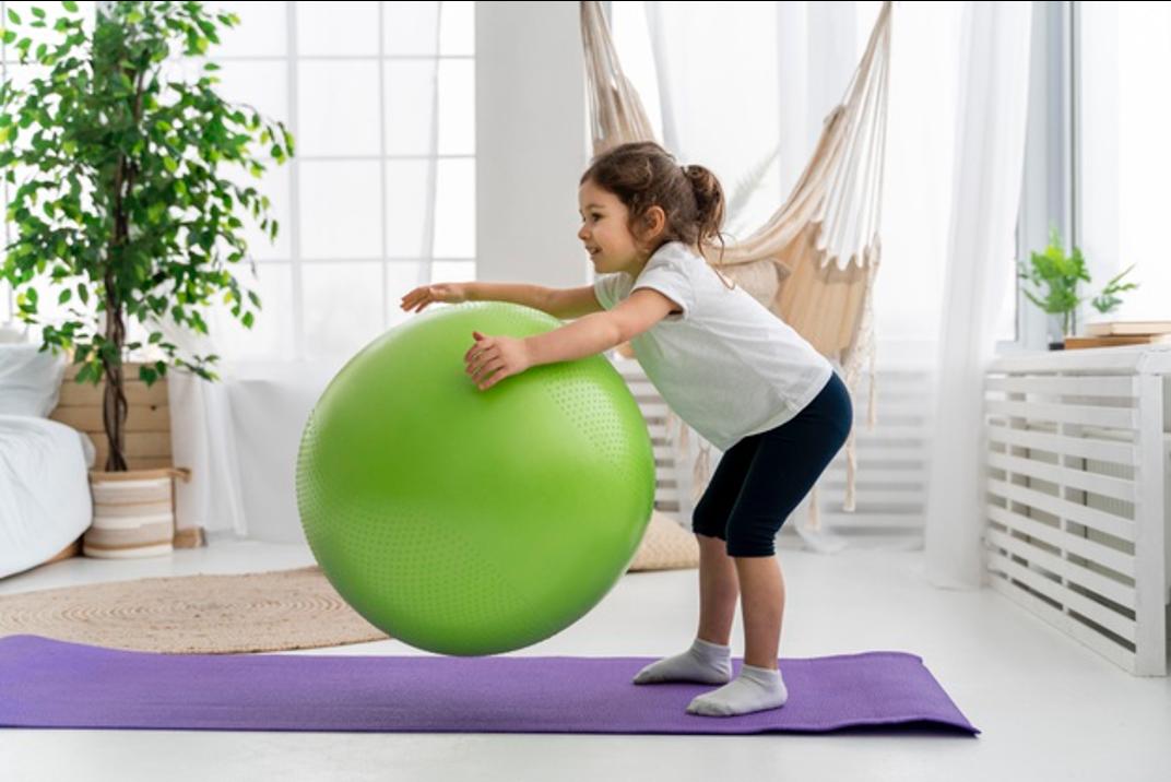 young child lime green yoga ball