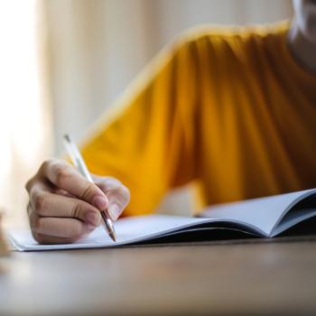 child in yellow shirt writing