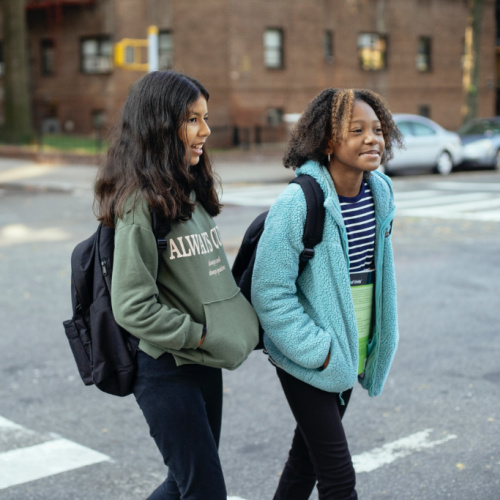2 children in backpacks crossing a street while chatting