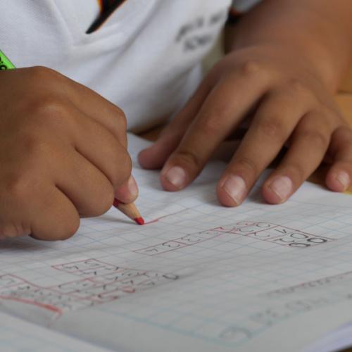 small hands writing math problem