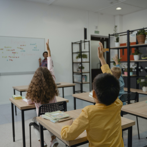 children in classroom with hands raised