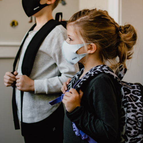 Pair of children wearing masks and backpacks