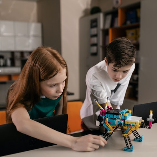 Two children making a LEGO robot.