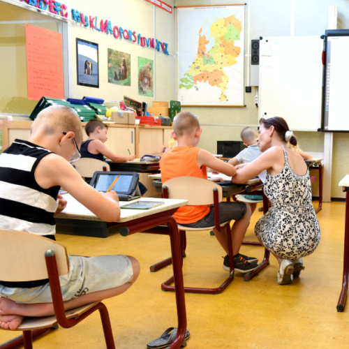 children in classroom with teacher crouched beside