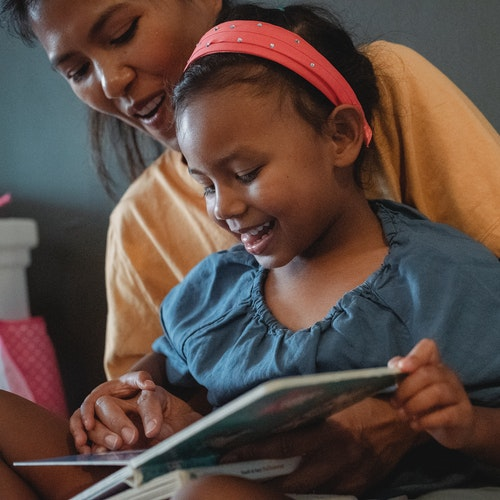 Mother and young daughter enjoying reading a book togehter