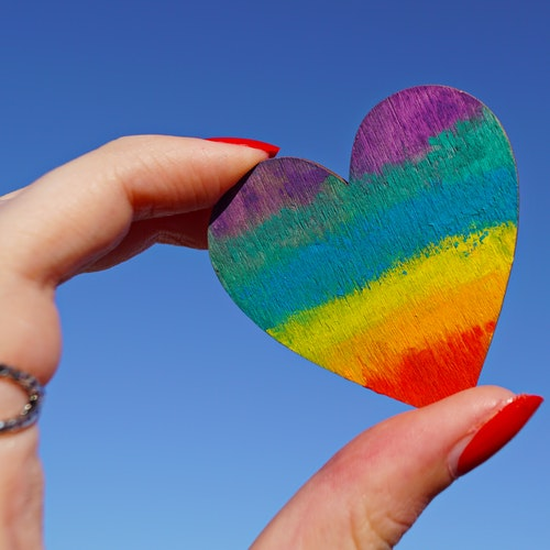 Rainbow-coloured heart being held between a thumb and finger against a blue background.