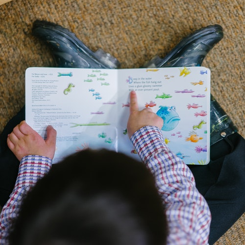 Overhead photo of a child reading a book.