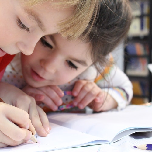 Two children writing in a notebook.