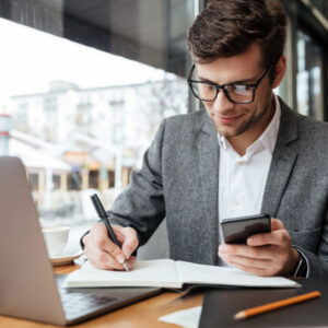 smiling-businessman-eyeglasses-sitting-by-table-cafe-with-laptop-computer-while-using-smartphone-writing-something