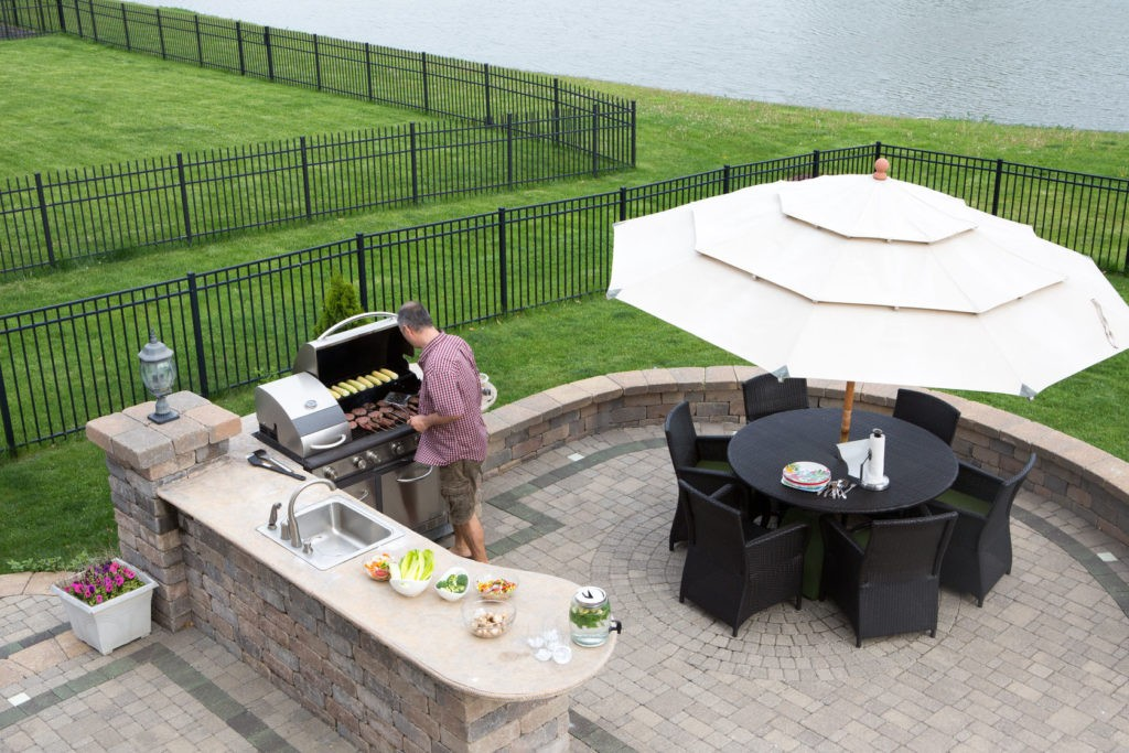 28265194 - high angle view of a man cooking meat on a gas bbq standing in the sunshine on a paved outdoor patio at the summer kitchen preparing for guests with a table and chairs with a garden umbrella alongside