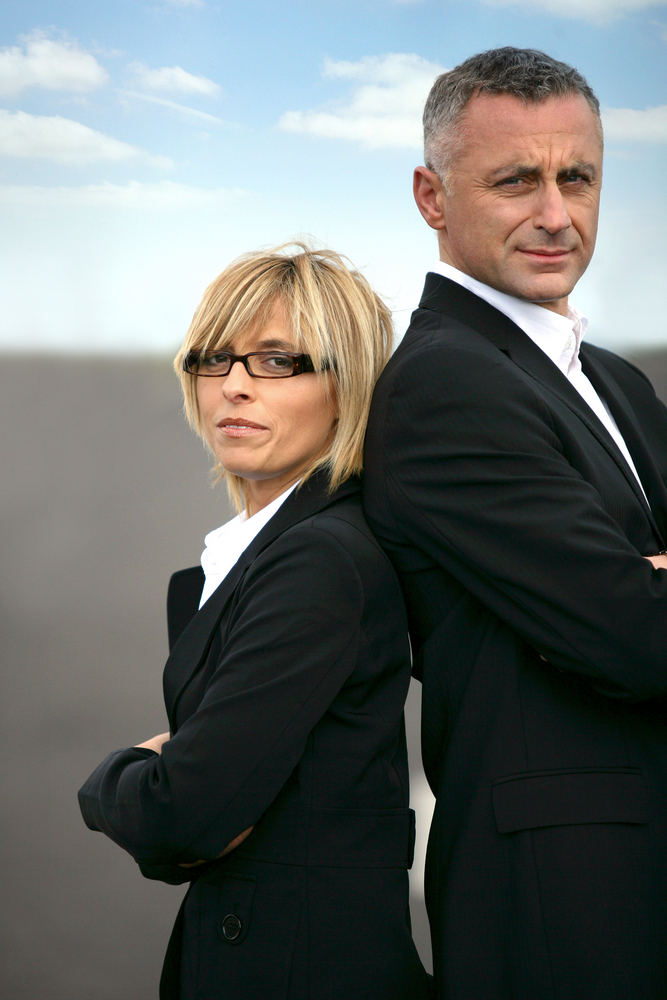 business woman and man standing back to back