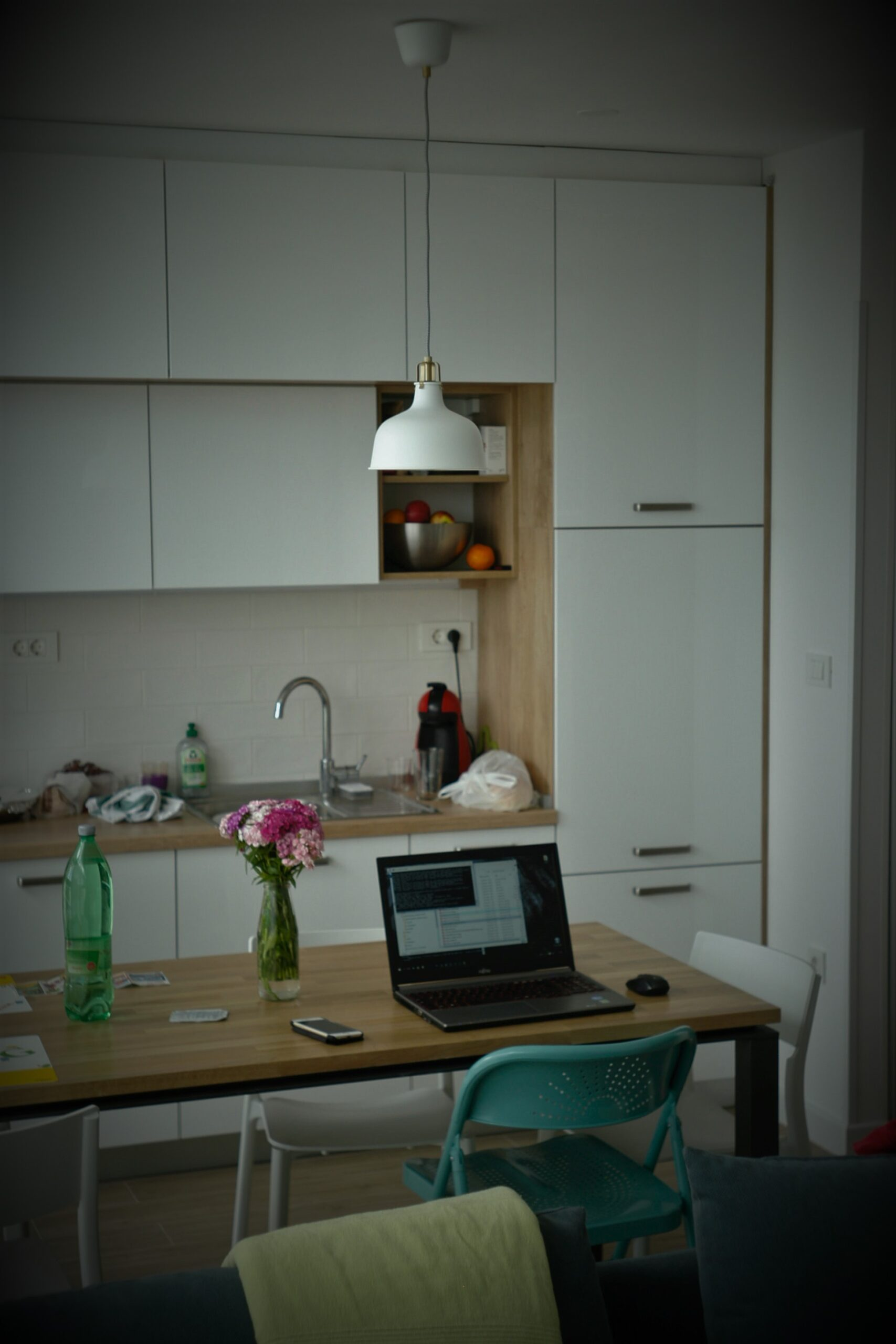 Image of poorly-lit workspace using only ceiling light. Low vision reading lamps are essential to preventing eye strain.