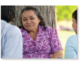 older native american woman talking with others near tree