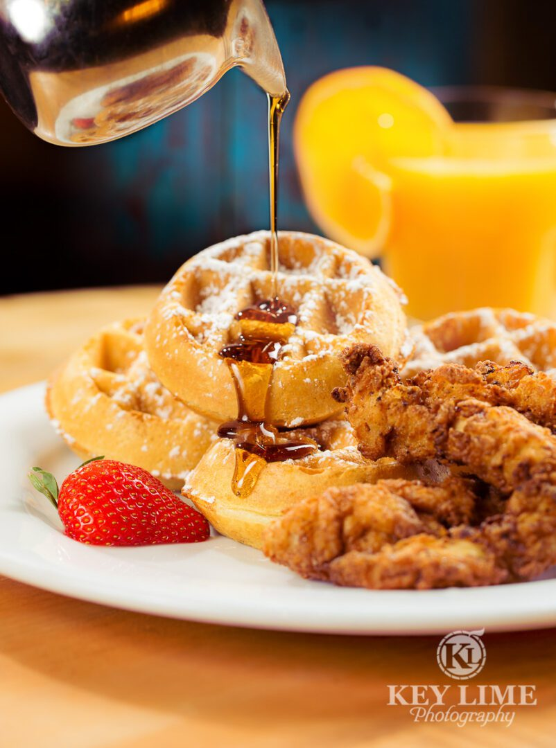 Food photographer in Las Vegas image of chicken and waffles. Strawberry and orange juice