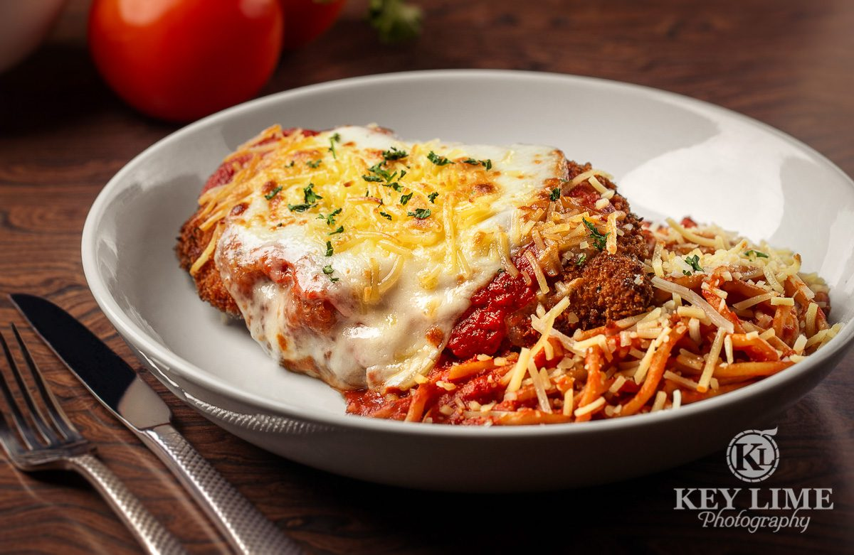 Chicken Parmesan image. Red sauce with a variety of cheeses. Food props include bright tomato.