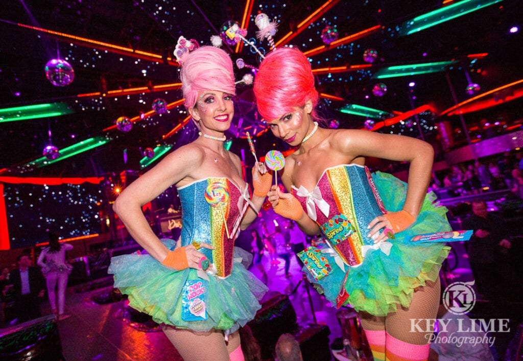 nightclub corporate event photographer image of two models dressed in candy outfits, smiling at the camera