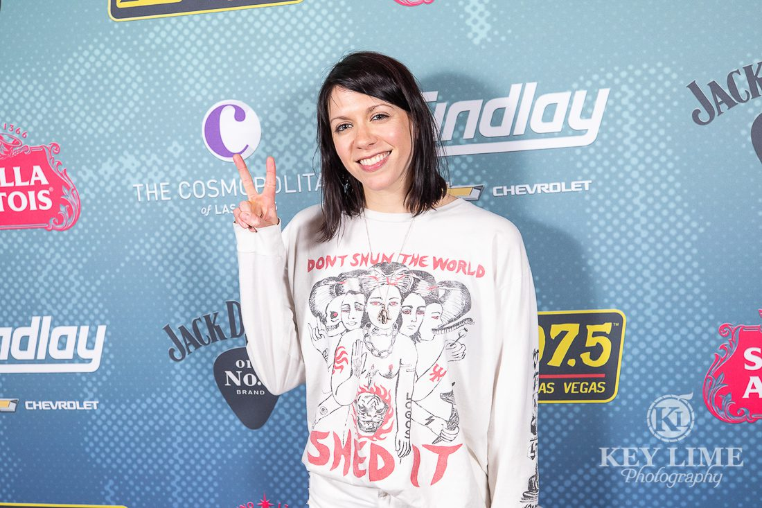 K.Flay smiling with a peace sign