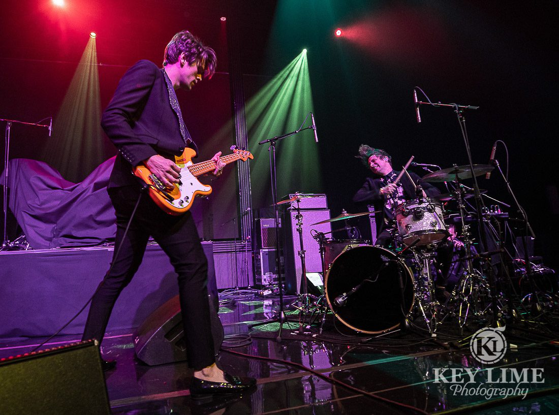 IDKHow - Holiday Concert Photographer image at Holiday Havoc 2019 in Las Vegas. Two band members onstage playing guitar and drums