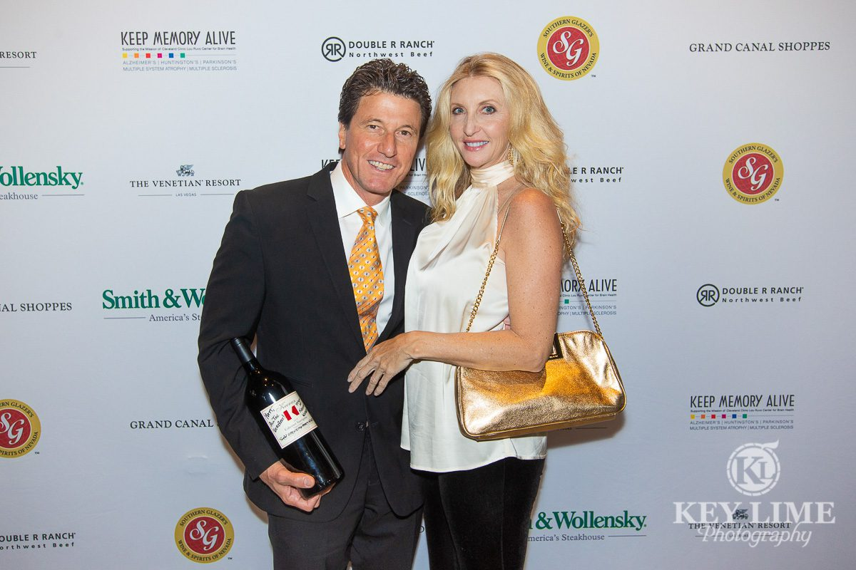 Red carpet entrance of the grand opening of Smith & Wollensky Las Vegas. Man and woman stand smiling with gift bottle.