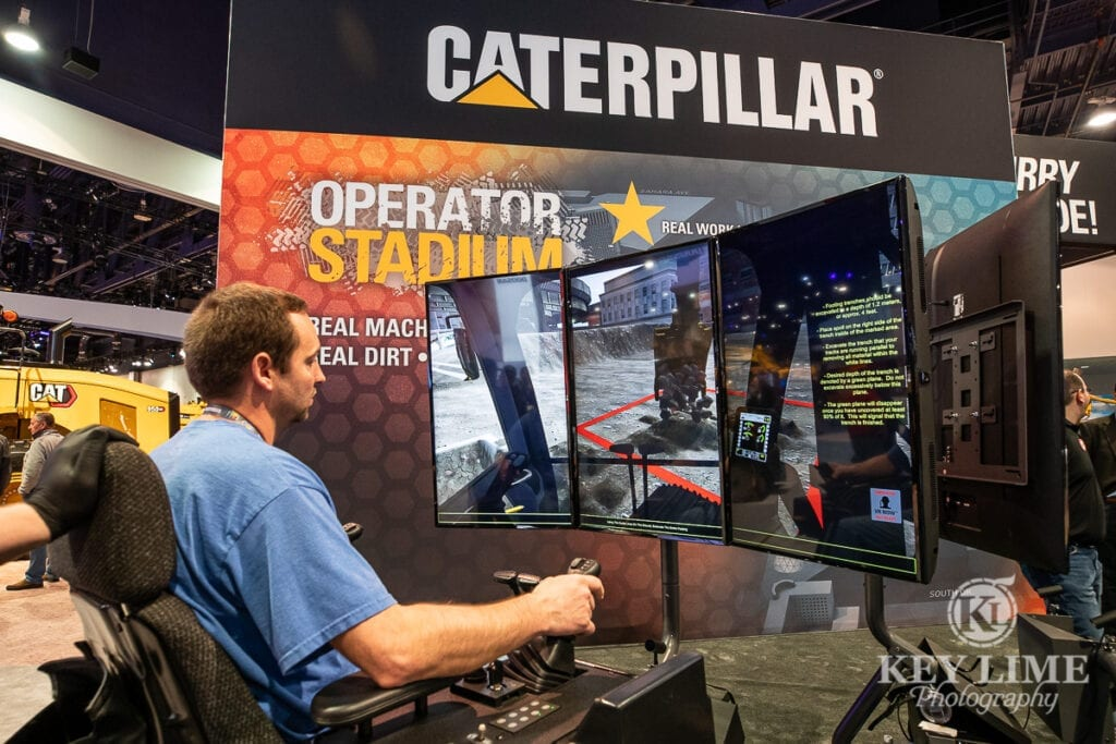 Construction photography of virtual backhoe heavy equipment video game, operator is sitting at controls that you would see in an actual vehicle and his view is simulated on a set of surrounding tv screens.