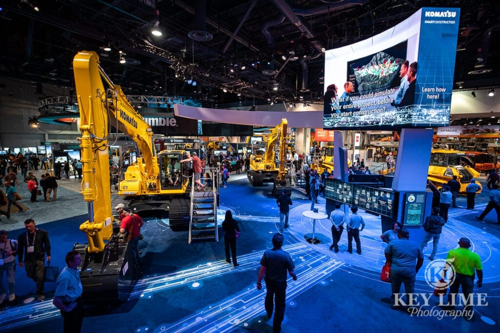 Komatsu, construction photography at CONEXPO, blue lighting effects and people standing near heavy equipment to show scale