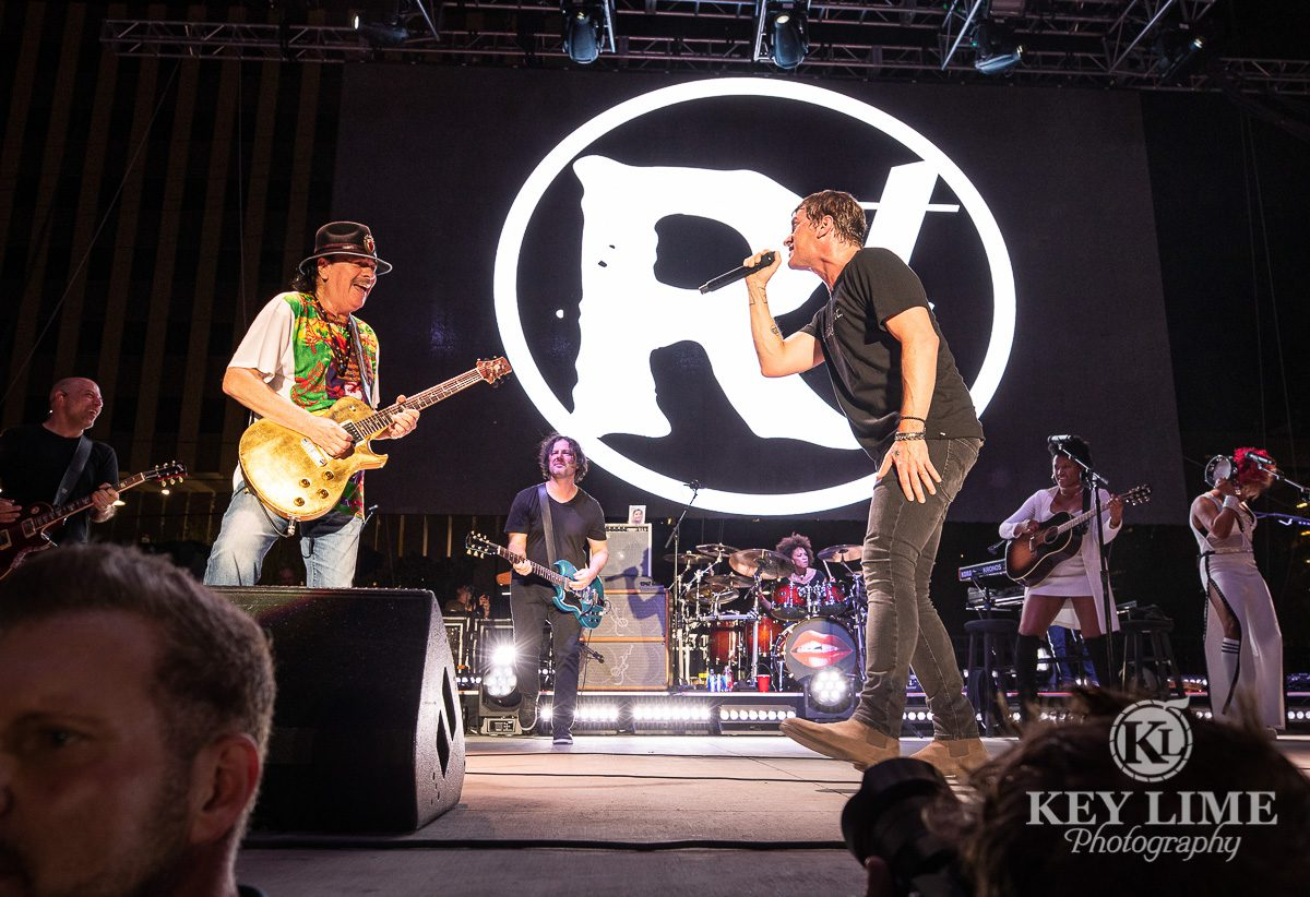 Event photography of Rob Thomas being joined by Santana for performance of Smooth, artists perfomring and smiling at each other